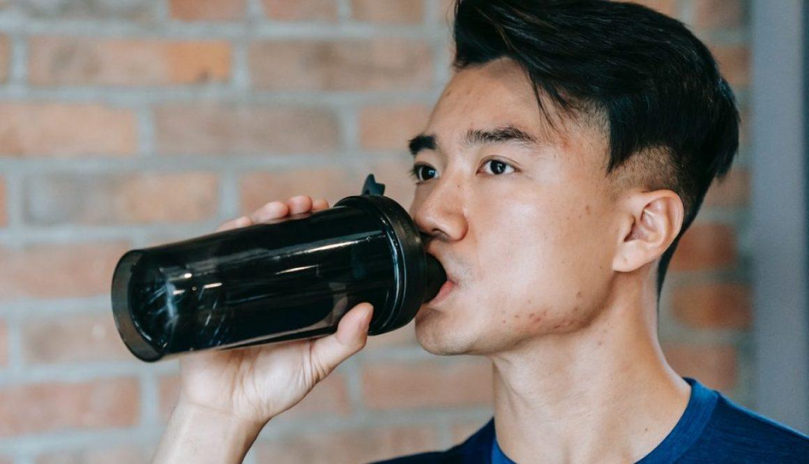 man in gym drinking vegan protein powder